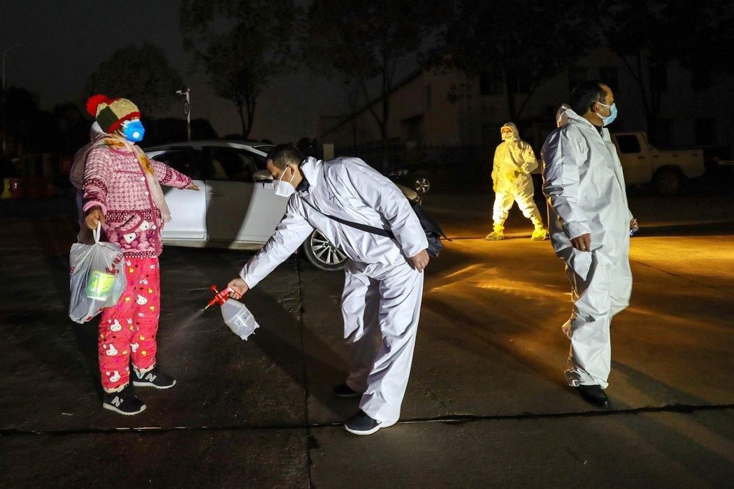 上周,医护人员为入住武汉一家隔离设施的人进行消毒。