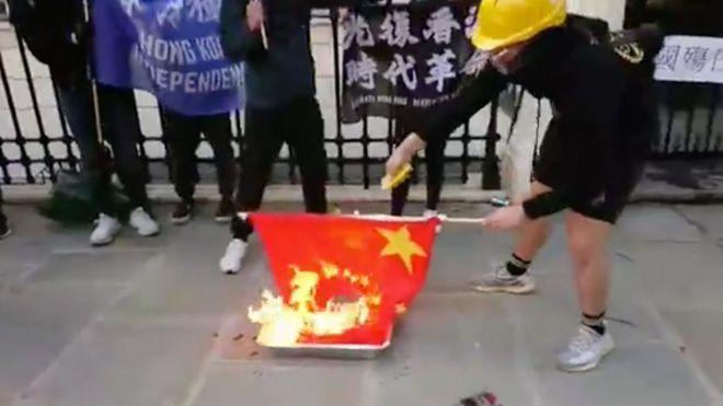 """10月1日 十多名香港人到伦敦的中国驻英国大使馆外示威。他们手持""""香港独立""""旗帜并焚烧中国国旗。"""